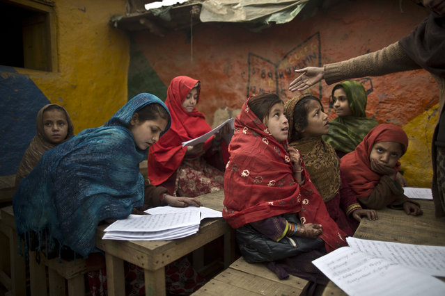 Afghan refugees and internally displaced Pakistani schoolgirls attend class at a makeshift school on the outskirts of Islamabad, Pakistan, Monday, January 12, 2015. Pakistani children and staff returned to a school in northwestern Pakistan where Taliban gunmen nearly a month ago killed 150 people – almost all of them students. (Photo by Muhammed Muheisen/AP Photo)