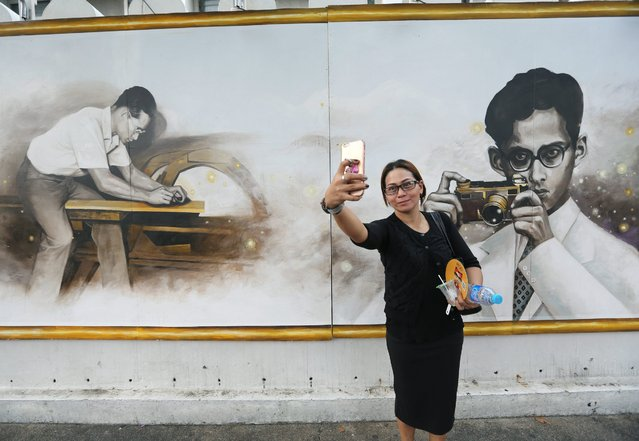 A Thai mourner taking a selfie with a large portrait of late Thai King Bhumibol Adulyadej, painted by Thai art students and installed on the wall at Silpakorn University, as part of the country's mourning for the Thai King, in Bangkok, Thailand, 18 October 2016. King Bhumibol, the world's longest reigning monarch died at the age of 88 in the Siriraj hospital in Bangkok on 13 October 2016. (Photo by Narong Sangnak/EPA)