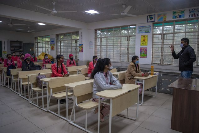 Students wearing face masks as a precaution against the coronavirus, attend classes as schools reopen after being closed for months due to the COVID-19 pandemic in New Delhi, India, Monday, January 18, 2021. Delhi on Monday opened schools for students of grade 10 and 12 after a gap of more than nine months. (Photo by Altaf Qadri/AP Photo)
