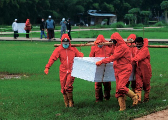 Municipality workers, wearing personal protective equipment (PPE), carry the coffin of a coronavirus victim at a burial area provided by the government for the victims of the coronavirus disease (COVID-19), as the outbreak continues in Jakarta, Indonesia, February 2, 2021. (Photo by Ajeng Dinar Ulfiana/Reuters)