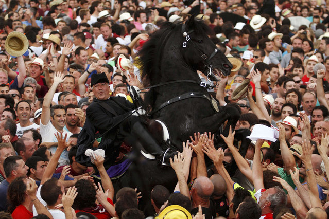A rider rears up on his horse while surrounded by a cheering crowd during the traditional Fiesta of San Joan (Saint John) in downtown Ciutadella, on the Spanish Balearic Island of Menorca, June 23, 2013. The riders of the horses are representatives of ancient Ciutadella society – nobility, clergy, craftsmen and farmers. (Photo by Enrique Calvo/Reuters)