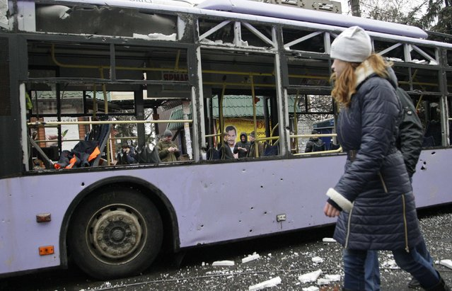 A woman walks past a damaged trolleybus in Donetsk, January 22, 2015. (Photo by Alexander Ermochenko/Reuters)