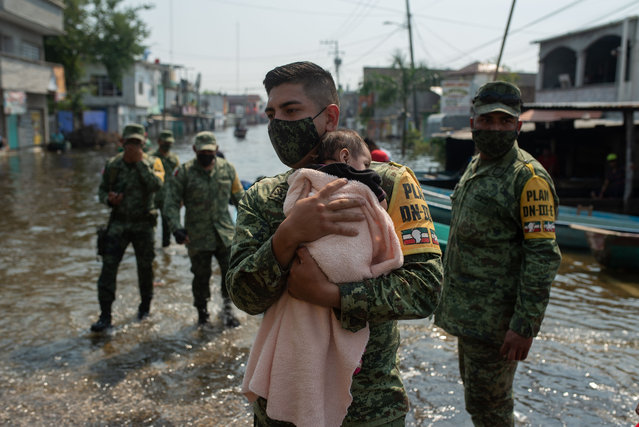 A Mexican soldier carries a baby on a flooded street after heavy rains in Villahermosa, state of Tabasco, Mexico, on November 11, 2020. (Photo by Angel Hernandez/AFP Photo)
