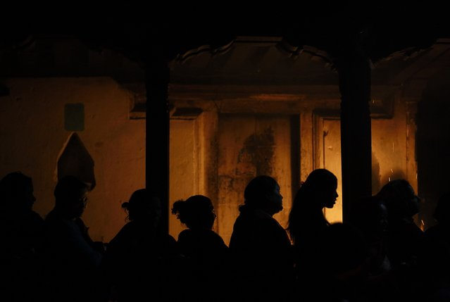 Devotees are silhouetted as they stand in a queue to enter a temple during the Swasthani Bratakatha festival at Panauti near Kathmandu January 24, 2015. (Photo by Navesh Chitrakar/Reuters)