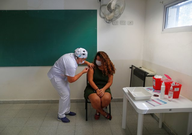 A woman receives a first dose of the Sputnik V (Gam-COVID-Vac) vaccine, as Argentina continues its inoculation campaign, in Buenos Aires, Argentina on February 19, 2021. According to the Argentine Health Ministry, more than 600,000 doses have already been administered. (Photo by Agustin Marcarian/Reuters)