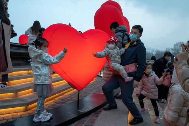 Residents wearing masks to protect from the coronavirus take photos amongst lit heart shaped balloons on Chinese Valentine's Day which coincides with the third day of the Chinese Lunar New Year in Beijing on Sunday, February 14, 2021. (Photo by Ng Han Guan/AP Photo)