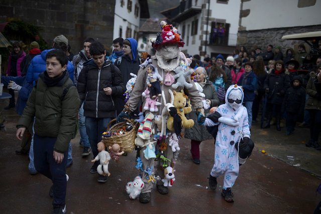 A man wearing a costume decorated with soft toys walks with a child during carnival celebrations in Zubieta January 27, 2015. (Photo by Vincent West/Reuters)