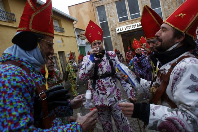 """Believers take a sip of alcohol while parading around town during the """"Endiablada"""" festival in Almonacid del Marquesado, in central Spain February 3, 2015. (Photo by Susana Vera/Reuters)"""