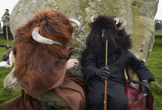 Two people wearing animal costumes  join others as people gather  to celebrate the Winter Solstice at Stonehenge in England  Tuesday December 22, 2015.  The winter solstice is celebrated by many people around the world as the beginning of the return of the sun. (Photo by Ben Birchall/PA Wire via AP Photo)