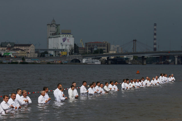 People take part in a mass baptism ceremony organized by Ukrainian Evangelists and Protestants as a part of celebration of the 1030-years anniversary of the Baptism of Kievan Rus, in the waters of the Dnipro River in Kiev, Ukraine July 22, 2018. (Photo by Valentyn Ogirenko/Reuters)