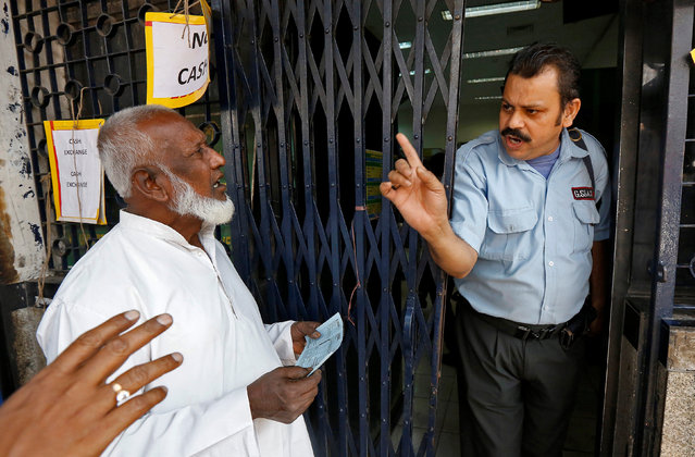 A security guard speaks with senior citizens queuing outside a bank to deposit or exchange their old high denomination banknotes in Kolkata, India, November 19, 2016. (Photo by Rupak De Chowdhuri/Reuters)