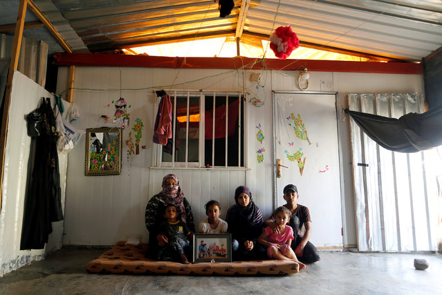 Afef Salem, 33, the Syrian widow of a rebel fighter, poses for a photograph with her children, as they hold a photograph of their late father in Zaatari camp in Jordan, October 14, 2016. Salem's husband was killed during fighting againt forces loyal to Syria's President Bashar al-Assad in Sheikh Saeed, Aleppo. (Photo by Ammar Awad/Reuters)