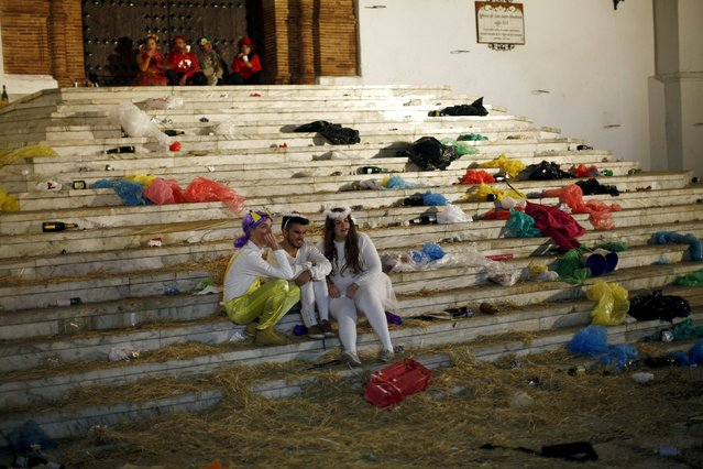 People sit on the stairs outside a church next to bottles of champagne and trash following New Year celebrations in Coin, near Malaga, southern Spain, January 1, 2016. (Photo by Jon Nazca/Reuters)