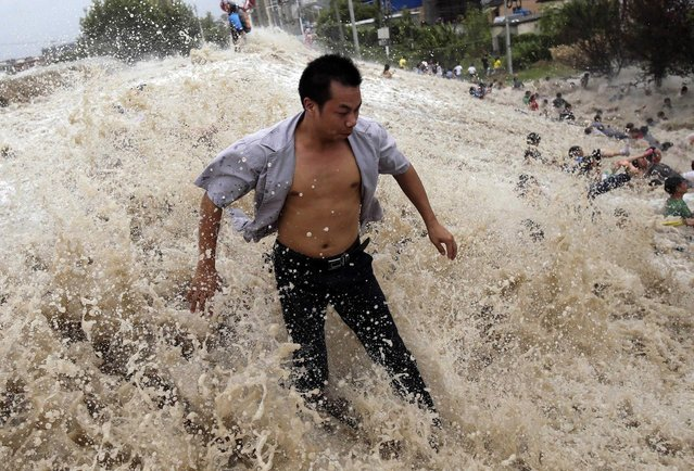 People struggle as waves from a tidal bore surge past a barrier on the banks of Qiantang River in Haining, Zhejiang province, August 22, 2013. As Typhoon Trami landed in eastern China, tidal level in Qiantang River was recorded at 6.6 metre high with surge reaching 1.3 metre high, local media reported. (Photo by Reuters/China Daily)