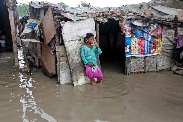 A girl brushes her teeth as she stands outside her submerged shanty at a slum area after a rise in the waters of the river Yamuna in New Delhi, India, July 31, 2018. (Photo by Adnan Abidi/Reuters)