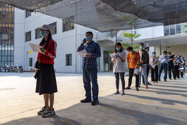 In this photo released by Xinhua News Agency, residents wearing masks line up for COVID-19 vaccination at the Jingcheng Hospital in Ruili city in southwestern China's Yunnan Province, April 1, 2021. The Chinese border city hit by a fresh outbreak of COVID-19 this week began a five-day drive Friday to vaccinate its entire population of 300,000 people. (Photo by Chen Xinbo/Xinhua via AP Photo)