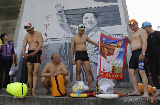 Swimmers hold a flag with an image of Mao Zedong printed on it before they set off swimming in the Yangtze to mark International Labor Day in Wuhan, Hubei province, May 1, 2013. (Photo by Darley Shen/Reuters)