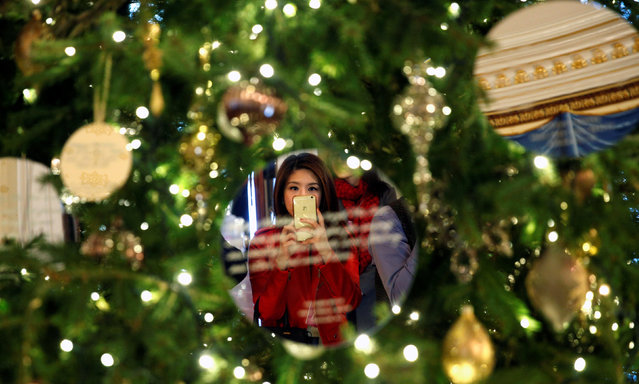 Reflected in an ornament, a reporter takes a photo of the White House Christmas Tree in the Blue Room during a media preview of the holiday decor at the White House in Washington, U.S., November 29,  2016. (Photo by Kevin Lamarque/Reuters)