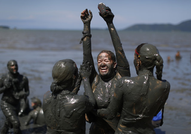 "Revelers cover a freind in mud during the traditional ""Bloco da Lama"" or ""Mud Block"" carnival party, in Paraty, Brazil, Saturday, February 14, 2015. (Photo by Leo Correa/AP Photo)"