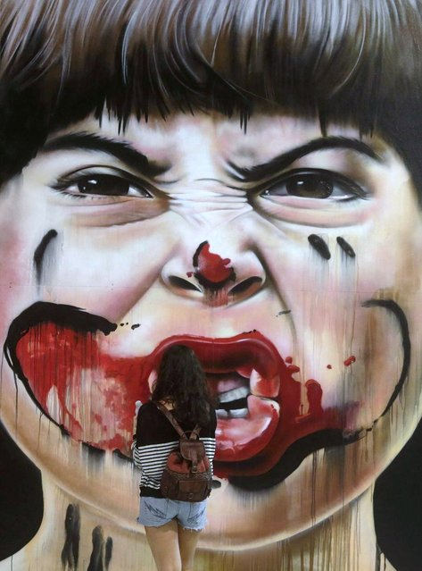 A visitor observes a work by Zack during the Art Rua street art festival in Rio de Janeiro, on September 7, 2013. (Photo by Ricardo Moraes/Reuters)