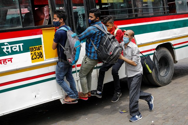 Migrant workers hang on to a door of a moving bus as they return to their villages after Delhi government ordered a six-day lockdown to limit the spread of the coronavirus disease (COVID-19), in Ghaziabad on the outskirts of New Delhi, India, April 20, 2021. (Photo by Adnan Abidi/Reuters)