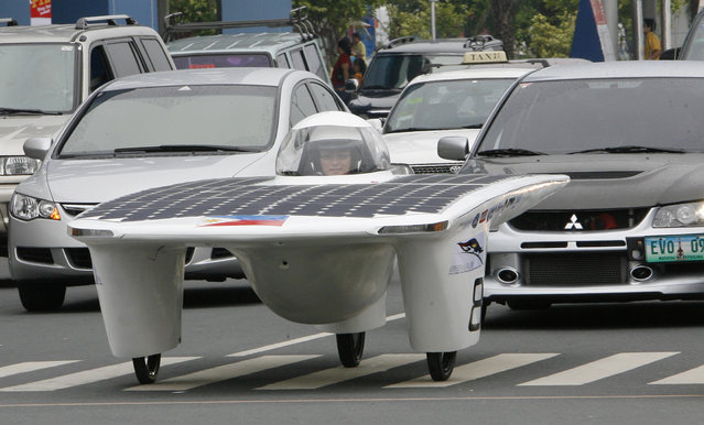Eric Tan, one of the students who designed and constructed the first Philippine solar-powered car, drives past vehicles along a street in Manila September 1, 2007, after it was unveiled. (Photo by Romeo Ranoco/Reuters)