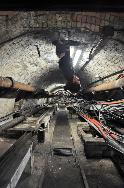 An urban explorer dangles upside down as he enters the Embankment Cable Run on the north bank of the River Thames in London. (Photo by Bradley L. Garrett/Barcroft Media)