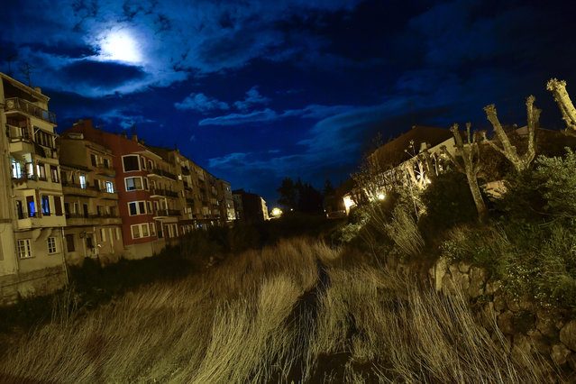 A moon light illuminates the sky through the clouds over a large line of grass between some home houses in the small village of Tafalla, northern Spain, Tuesday, May 1, 2018. (Photo by Alvaro Barrientos/AP Photo)
