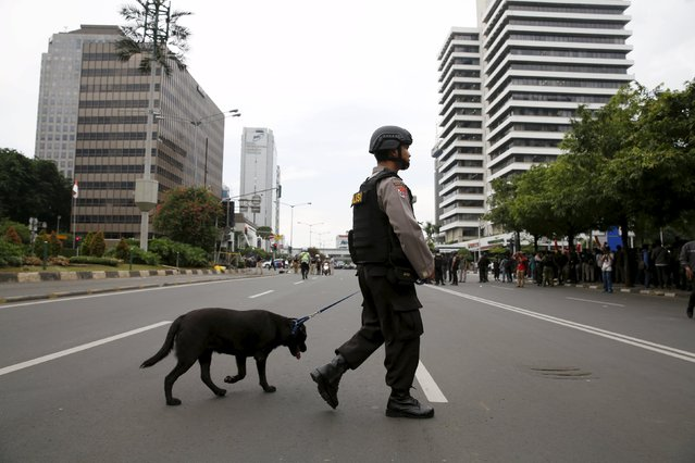 An Indonesian policeman carries a dog while patrolling at Thamrin business district in Jakarta, January 14, 2016. (Photo by Reuters/Beawiharta)
