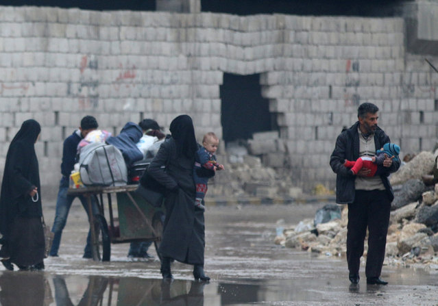 Civilians carry their belongings as they flee deeper into the remaining rebel-held areas of Aleppo, Syria December 7, 2016. (Photo by Abdalrhman Ismail/Reuters)
