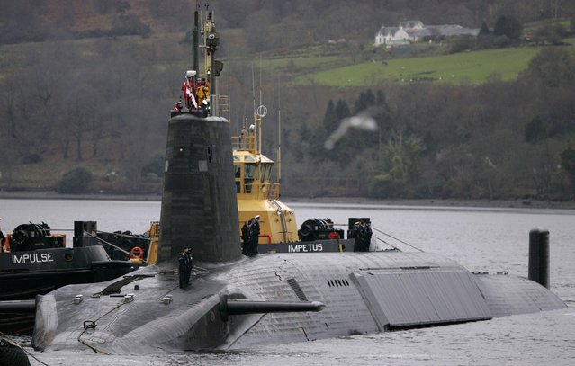 Crew from HMS Vengeance, a British Royal Navy Vanguard class Trident Ballistic Missile Submarine, stand on their vessel as they return along the Clyde river to the Faslane naval base near Glasgow, Scotland December 4, 2006. (Photo by David Moir/Reuters)