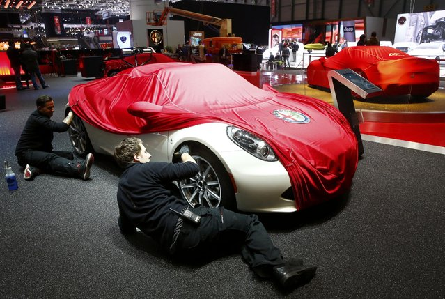 Employees prepare an Alfa Romeo 4C Spider car ahead of the 85th International Motor Show in Geneva, March 2, 2015.           REUTERS/Arnd Wiegmann (SWITZERLAND  - Tags: TRANSPORT BUSINESS)