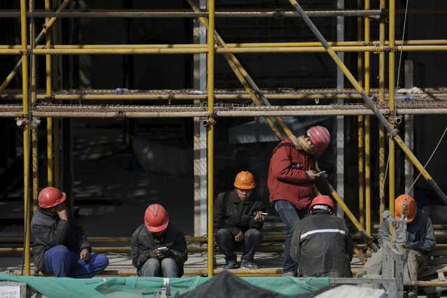 Workers rest after lunch at a construction site in Shanghai, China, January 19, 2016. China's economic growth eased to 6.8 percent in the fourth quarter from a year earlier, matching expectations but still the slowest since the global financial crisis, putting pressure on policymakers to roll out more support measures as fears of a sharper slowdown pummel global financial markets. (Photo by Aly Song/Reuters)