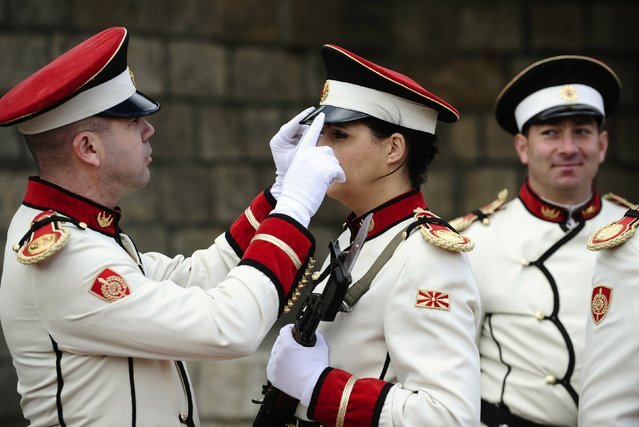 A soldier adjusts the hat of Corporal Verica Zlatevska during an honour guard training session at an army barracks in Skopje March 4, 2015. Macedonia's honour army battalion, the ceremonial uniformed guard that receives every foreign president, dignitaries and delegations, but also sees off and welcomes the head of state every time he leaves the country, has a different glow. For the first time in the history of Macedonia's army, the honour guard has two women in its ranks. There has not been an event in which one of them is not in the first row. Zlatevska joined the army in 2003, Dragana Kitanovska in 2006. Picture taken March 4, 2015.   REUTERS/Ognen Teofilovski (MACEDONIA - Tags: MILITARY SOCIETY)