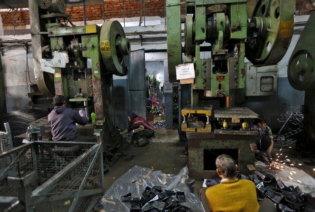Workers make auto parts on machines inside a manufacturing unit in Faridabad, India, December 24, 2015. Car makers such as Maruti Suzuki India and Hyundai Motor see huge growth in India, set to become the world's third-largest auto market by 2020 as millions buy their first new car. Price tags can be as low as $3,000 for a new Tata Motors Nano mini-car. India is also becoming a low-cost export hub for global car makers such as General Motors and Ford Motor. (Photo by Adnan Abidi/Reuters)