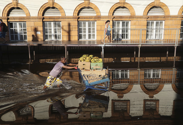 A man pushes a shopping cart loaded with bananas on a street flooded by the Negro River, in downtown Manaus, Amazonas state, Brazil, Tuesday, June 1, 2021. Rivers around Brazil's biggest city in the Amazon rain forest have swelled to levels unseen in over a century of record-keeping, according to data published Tuesday by Manaus' port authorities. (Photo by Edmar Barros/AP Photo)