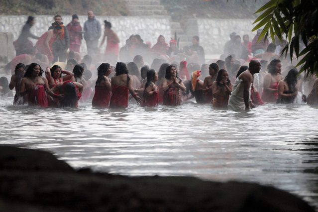Nepalese Hindu women take holy dips at the Salinadi River on the first day of  month long Swasthani Bratakatha festival, in Sankhu, outskirts of Katmandu, Nepal, Sunday, January 24, 2016. During this festival, devotees recite holy scriptures dedicated to Hindu goddess Swasthani and Lord Shiva. Unmarried women pray to get a good husband while those married pray for the longevity of their husbands by observing a month-long fast. (Photo by Niranjan Shrestha/AP Photo)