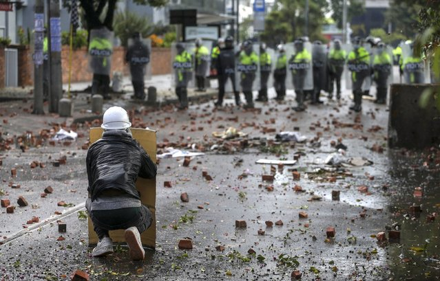 Anti-government protesters clash with the police in Bogota, Colombia, Wednesday, June 9, 2021. The protest have been triggered by proposed tax increases on public services, fuel, wages and pensions. (Photo by Ivan Valencia/AP Photo)