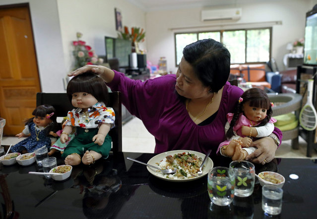 A picture made available on 25 January 2016 shows Thai devotee Ratchada Mahanavanont, 45, talking and patting her Child Angels Dolls while having a meal at her house in Bangkok, Thailand, 24 January 2016. The new superstitious trend among Thai people involves carrying, talking and caring for factory-manufactured dolls (called 'Look Thep' in Thai). They believe the dolls hold children's spirits which bring good luck, wealth, blessing and protection from harm. Child Angels dolls owners worship and treat them as human infants by cradling, feeding and dressing up them up. (Photo by Rungroj Yongrit/EPA)