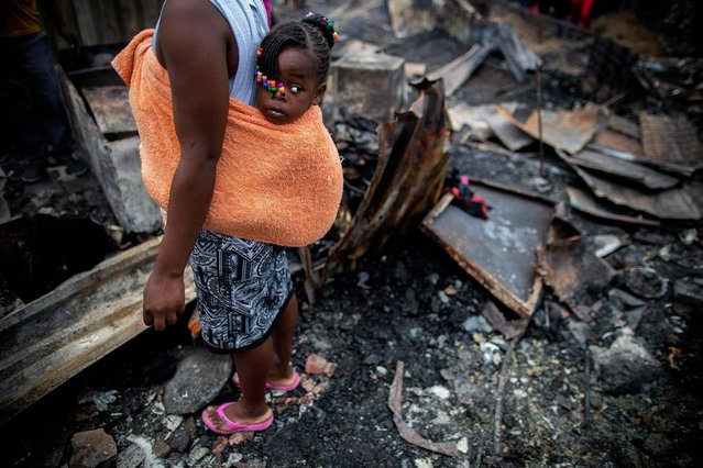 A baby girl looks on as her mother a resident of Masiphumelele informal settlement salvages material after a fire destroyed over 40 structures in Masiphumelele, Cape Town, South Africa 29 October 2018. Disaster Risk Management report 120 residents have been displaced due to the fire which was fanned by strong winds and ripped through backyard dwellings destroying a combination of shacks and formal houses. The high density living conditions caused the fire to spread rapidly. The cause is yet unknown. Disaster Risk Management is assisting survivors with food, shelter and help with arranging new documents destroyed in the fire. Cape Town is heading into its fire season with hot, dry and windy conditions prevailing. (Photo by Nic Bothma/EPA/EFE)