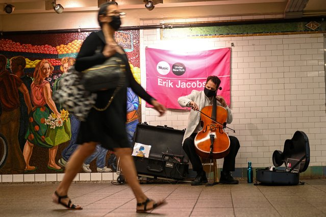 A woman walks past Cellist Erik Jacobson performing in the Times Square subway station as part of the Music Under New York Program on June 13, 2021 in New York City. The Music Under New York (MTA MUSIC) is one of the many programs created by the MTA in order to enhance the public's experience in the transit system New York Governor Andrew Cuomo lifted pandemic restrictions on May 19th. (Photo by Alexi Rosenfeld/Getty Images)