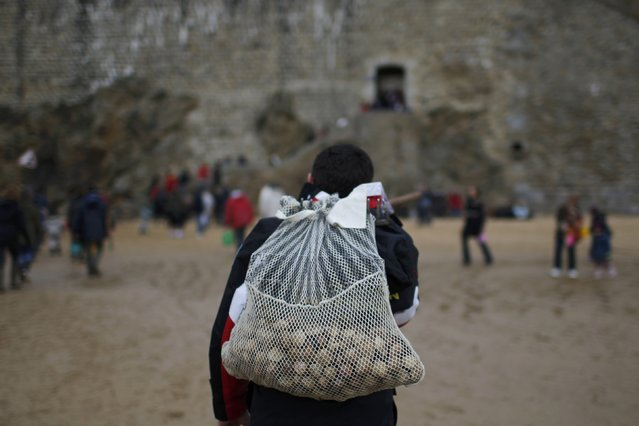A man carries a net with shellfish during a record low tide in Saint Malo, western France, March 21, 2015. (Photo by Stephane Mahe/Reuters)