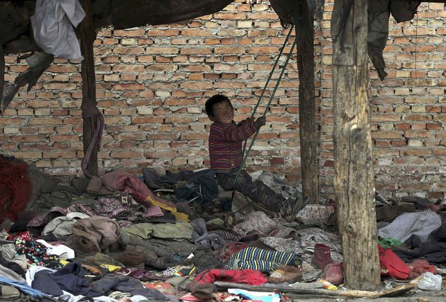 A boy, whose parents collect garbage for a living, plays on a makeshift swing at his dwelling, in Yuncheng, Shanxi province March 10, 2015. (Photo by Reuters/Stringer)