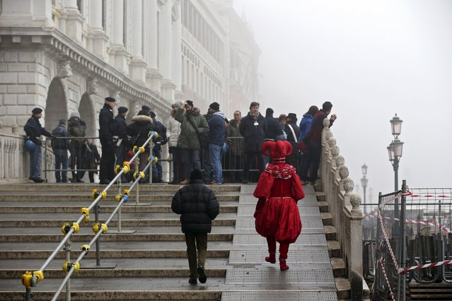 A masked reveller (R) walks before a check by Italian policemen in San Marco Piazza  during the Venice Carnival, January 31, 2016. (Photo by Alessandro Bianchi/Reuters)