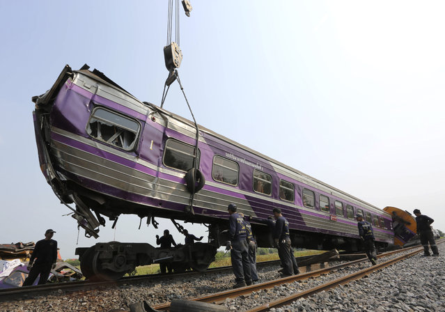 Thai workers remove wreckage of derailed train coaches at the site of a train accident in Ayutthaya province, Thailand, 27 March 2015. At least 52 people were injured in a train accident when two passenger trains crashed in the central province of Ayutthaya, official said. (Photo by EPA/Stringer)