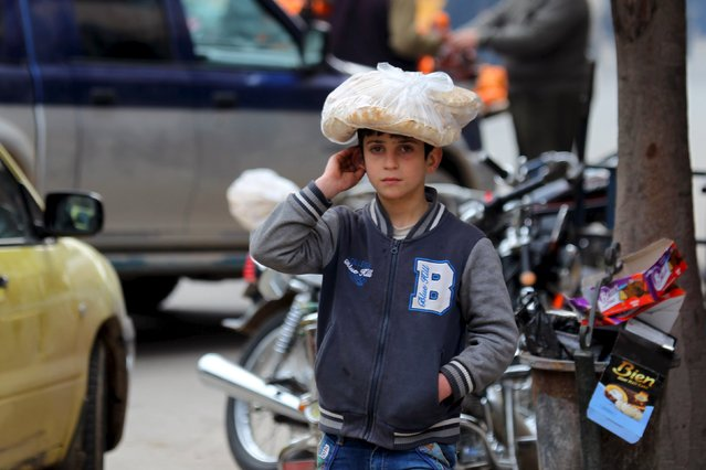 A boy carries bread on his head as he walks along a street in Idlib city, Syria January 23, 2016. (Photo by Ammar Abdullah/Reuters)