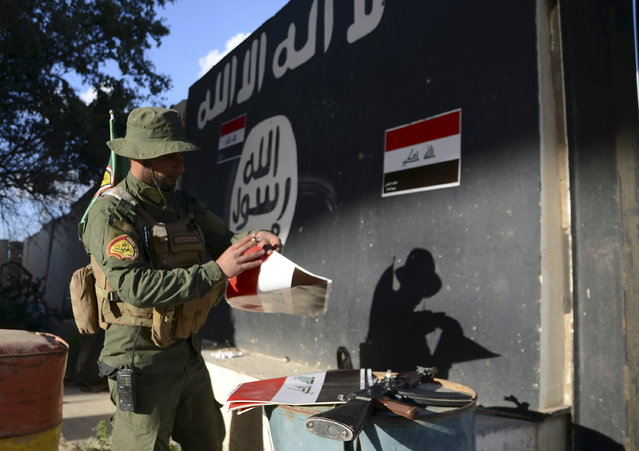 A Shi'ite paramilitary fighter puts Iraqi flags on a wall painted with the black flag commonly used by Islamic State militants in Tikrit March 31, 2015. (Photo by Reuters/Stringer)