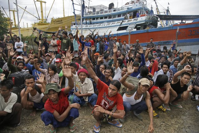 Burmese fishermen raise their hands as they are asked who among them want to go home at the compound of Pusaka Benjina Resources fishing company in Benjina, Aru Islands, Indonesia, Friday, April 3, 2015. Hundreds of foreign fishermen on Friday rushed at the chance to be rescued from the isolated island where an Associated Press report revealed slavery runs rampant in the industry. Indonesian officials investigating abuses offered to take them out of concern for the men's safety. (Photo by Dita Alangkara/AP Photo)