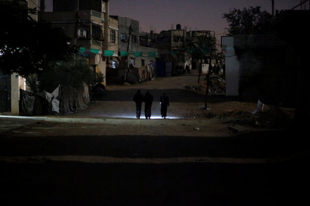 Palestinians walk on a road during a power cut in Beit Lahiya in the northern Gaza Strip January 11, 2017. (Photo by Mohammed Salem/Reuters)