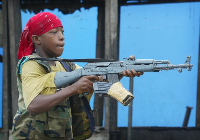 A child soldier loyal to the government fires at rebels July 23, 2003 at a key bridge in Monrovia, Liberia. (Photo by Chris Hondros/Getty Images)